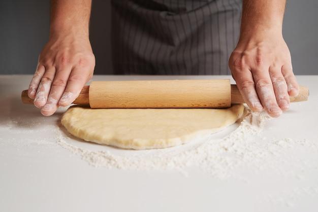 Szef kuchni rozciąga ciasto