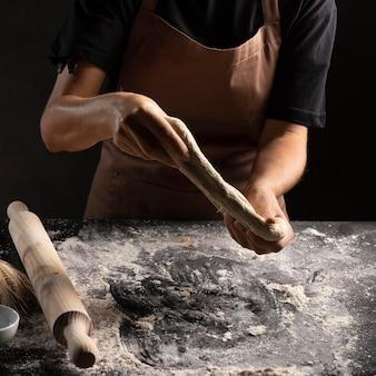 Szef kuchni rozciągający ciasto rękami