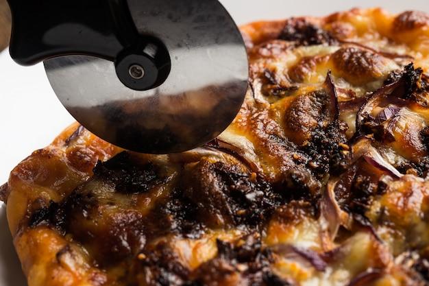 Szef kuchni rozdrabnia świeżo przygotowane plastry do pizzy