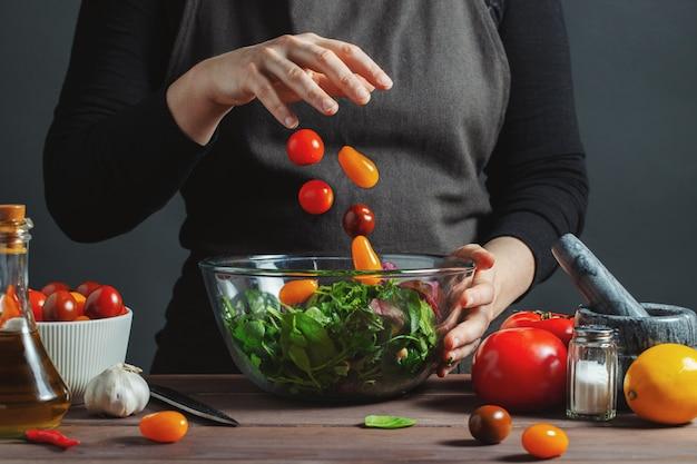 Szef kuchni rozlewa pomidory w misce