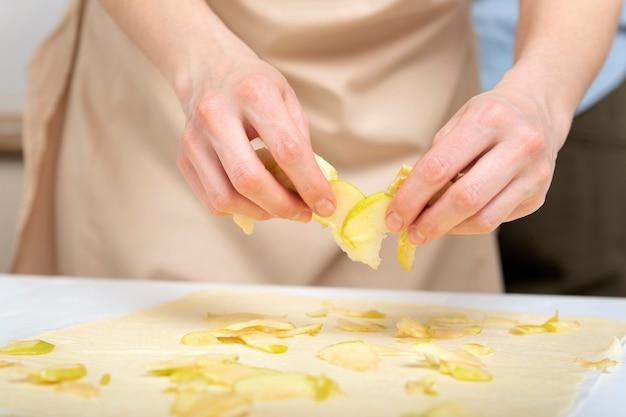 Szef kuchni rozprowadza plasterki jabłka na cienko rozwałkowanym cieście