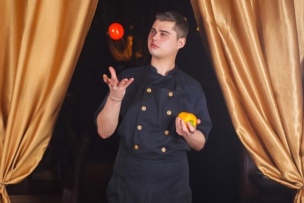 Szef kuchni rzuca pomidorem.