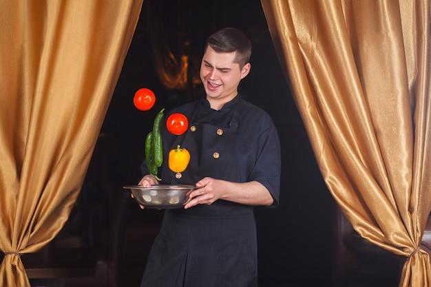 Szef kuchni rzuca świeże warzywa.