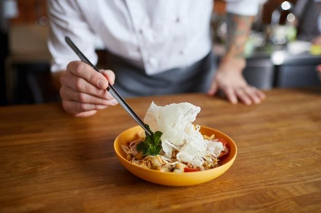 Szef kuchni serwujący dania kuchni azjatyckiej