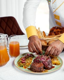 Szef kuchni serwujący grillowane steki wołowe z frytkami, keczupem i surówką