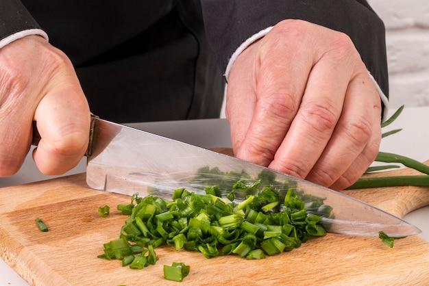 Szef kuchni sieka szczypiorek nożem