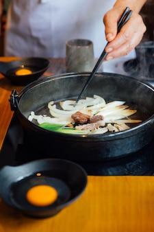Szef kuchni smażona cebula, scallion i grzyb w gorącym garnku sukiyaki.