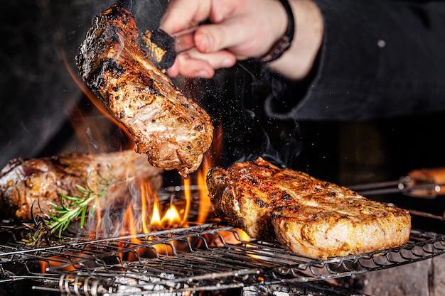 Szef kuchni smaży mięso, stek wołowy na otwartym ogniu w restauracji