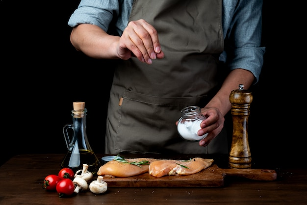 Szef kuchni solą pierś kurczaka