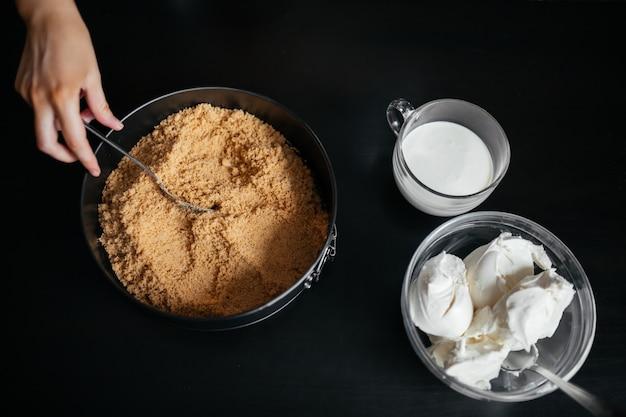 Szef kuchni stawia pokruszone produkty w naczyniu do pieczenia na czarnym stole