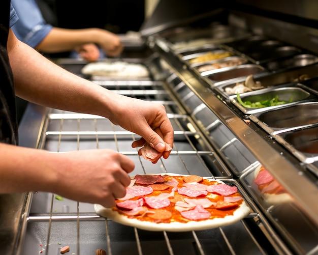 Szef kuchni stawia salami na cieście do pizzy pokrytym sosem pomidorowym