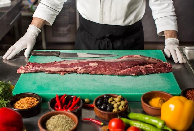 Szef kuchni stoi w kuchni, aby przygotować stek wołowy