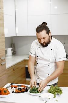 Szef kuchni stoi w kuchni w domu, gotuje