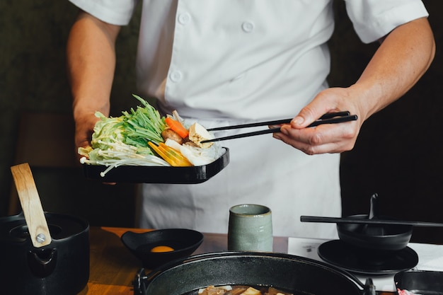 Szef kuchni szczypał warzywa w gorący garnek pałeczkami przed nalaniem zupy sojowej.