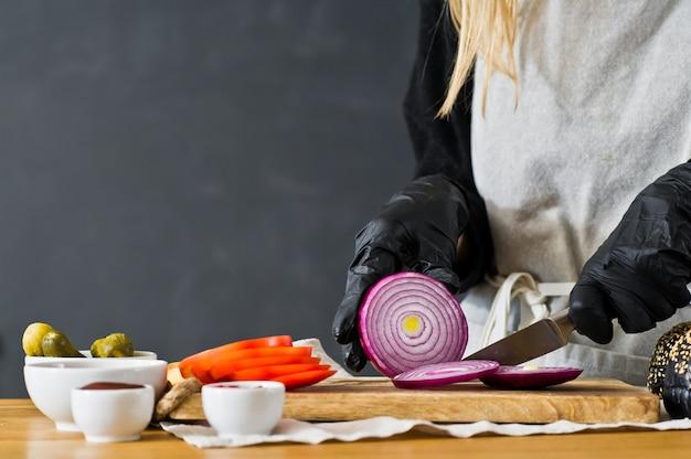 Szef kuchni tnie czerwoną cebulę. koncepcja gotowania czarnego burgera. przepis hamburgera domowej roboty.