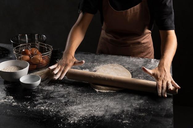 Szef kuchni toczy ciasto w stole