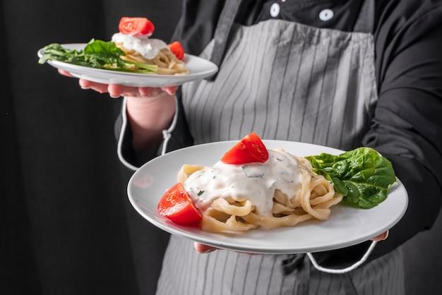 Szef kuchni trzyma danie z makaronem z sosem i pomidorami