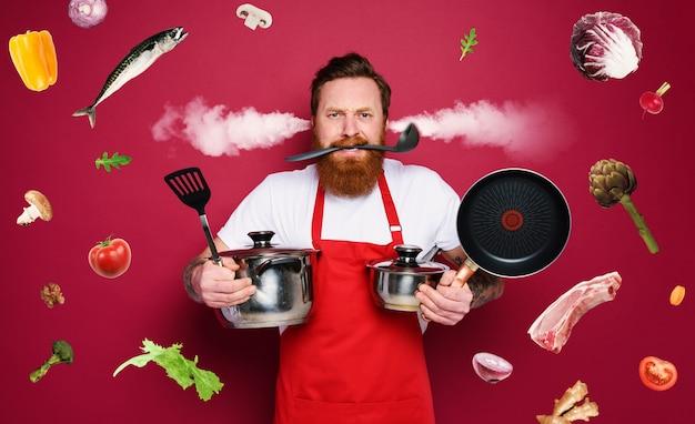 Szef kuchni trzyma dużo garnków. jest zestresowany z powodu przepracowania. czerwone tło