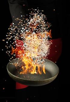 Szef kuchni trzyma okrągłą patelnię i wyrzuca mieszankę przypraw i białej soli