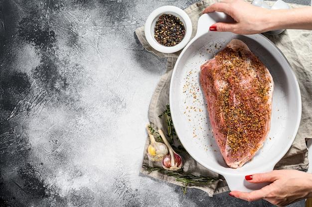 Szef kuchni trzyma patelnię ze świeżymi kawałkami wieprzowiny. surowe mięso z przyprawami. szare tło. widok z góry.