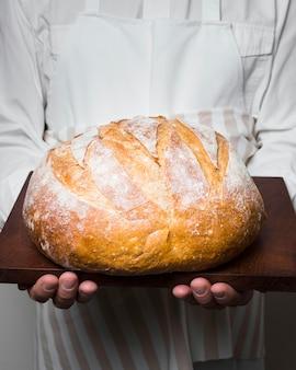 Szef kuchni trzyma pyszny okrągły chleb