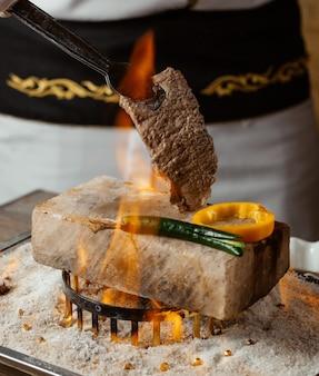 Szef kuchni trzyma stek wołowy na kamieniu z grillowaną papryką w ogniu