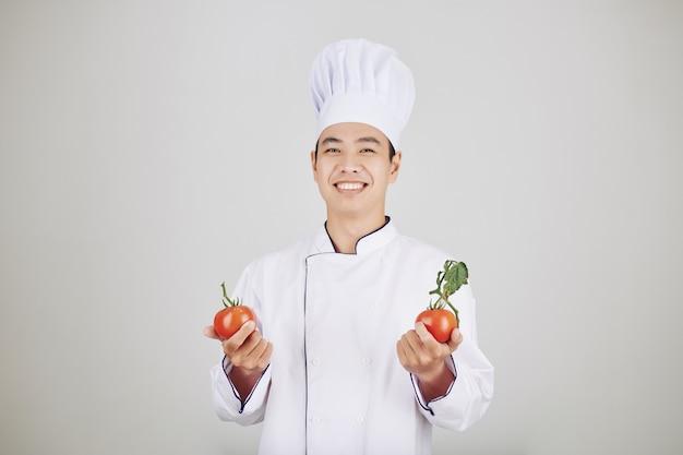 Szef kuchni trzyma świeże pomidory