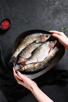 Szef kuchni trzyma talerz karpia. ryby ekologiczne rzeczne. czarne tło. widok z góry. miejsce na tekst