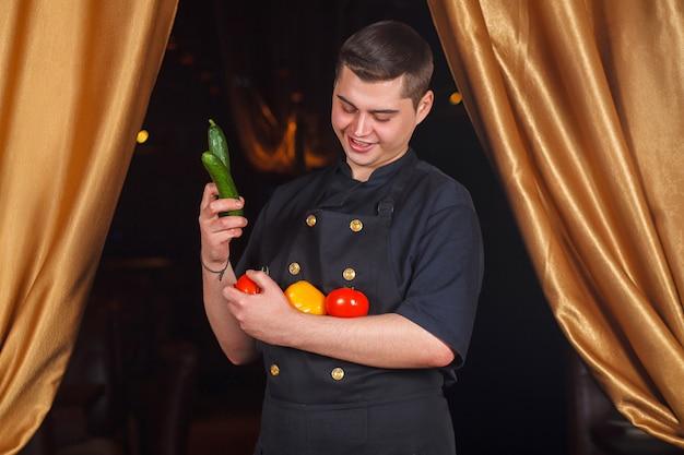 Szef kuchni trzyma warzywa w dłoniach
