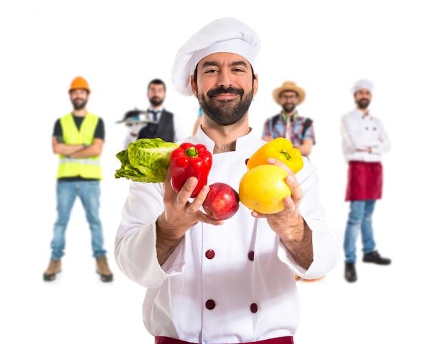 Szef kuchni trzyma warzywa