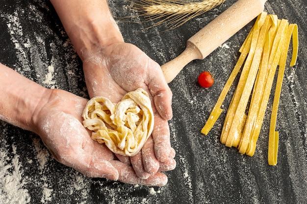 Szef kuchni trzymając w rękach niegotowane makarony