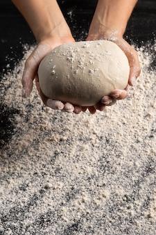 Szef kuchni, trzymając w rękach piłkę ciasta