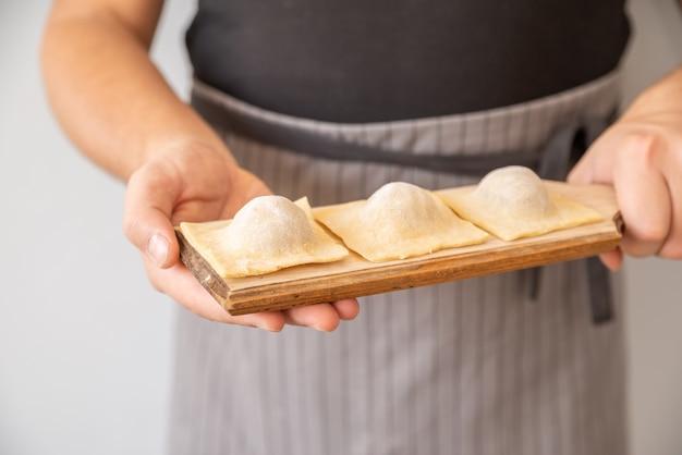 Szef kuchni trzymając wypełniony makaron