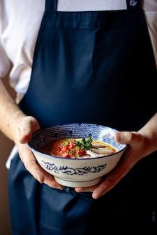 Szef kuchni trzymający miskę japońskiego ramen z kurczaka curry