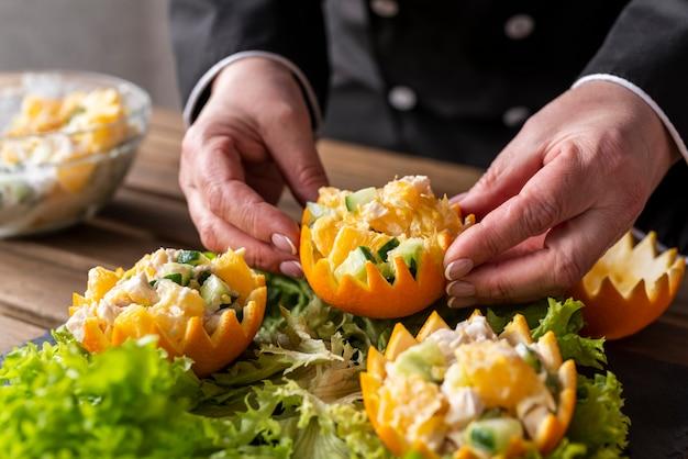 Szef kuchni układa danie z sałatką i pomarańczami