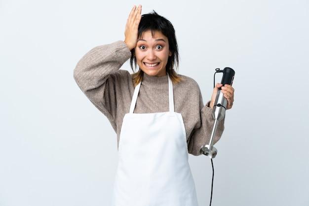 Szef kuchni urugwajska dziewczyna za pomocą ręcznego miksera na pojedyncze białe z niespodzianką wyraz twarzy