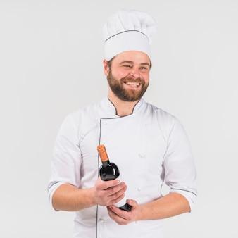 Szef kuchni uśmiecha się z butelką wina