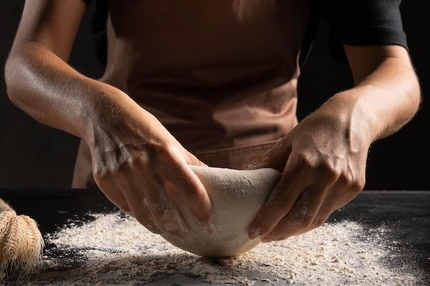 Szef kuchni używa mąki do zagniatania ciasta, aby nie przykleiło się do dłoni