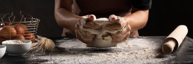 Szef kuchni używa rąk do wyrabiania ciasta
