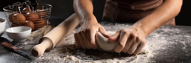 Szef kuchni używa rąk i mąki do zagniatania ciasta