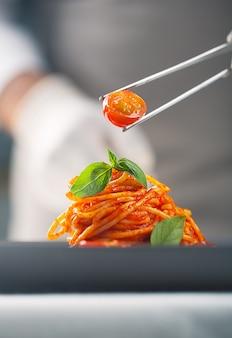 Szef kuchni w białym mundurze i rękawiczkach serwuje pomidorki koktajlowe w makaronie w sosie pomidorowym z listkami bazylii za pomocą pęsety. wykwintna kuchnia. jedzenie na talerzu