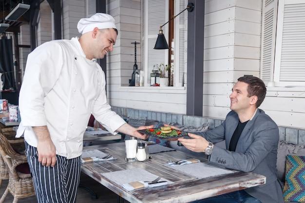 Szef kuchni w białym mundurze serwuje nowe danie dla klienta restauracji