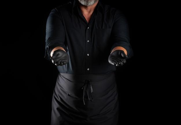 Szef kuchni w czarnej koszuli, fartuchu i lateksowych czarnych rękawiczkach stoi na czarnej przestrzeni, jego ramiona są wyciągnięte do przodu, trzymając przedmiot