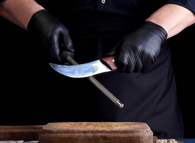Szef kuchni w czarnej koszuli i czarnych lateksowych rękawiczkach ostrzy nóż kuchenny na żelaznej ostrzałce z uchwytem