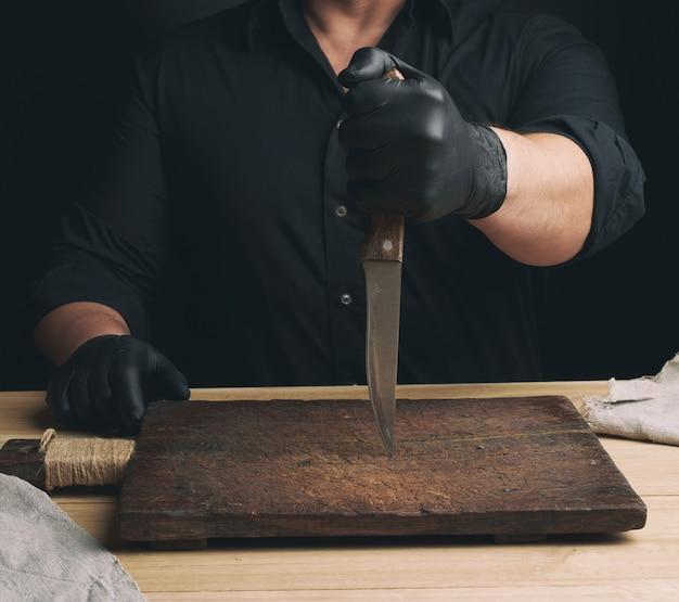 Szef kuchni w czarnej koszuli i czarnych lateksowych rękawiczkach trzyma duży nóż kuchenny