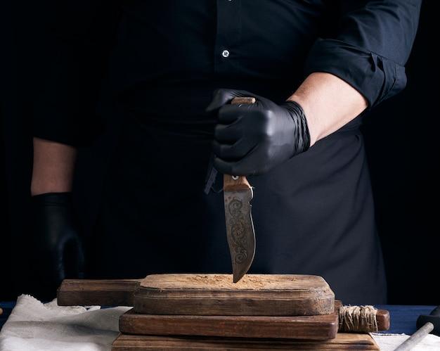 Szef kuchni w czarnej koszuli i czarnych lateksowych rękawiczkach trzyma klasyczny nóż kuchenny