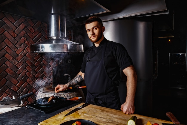 Szef kuchni w czarnej tuniki gotuje w restauracji
