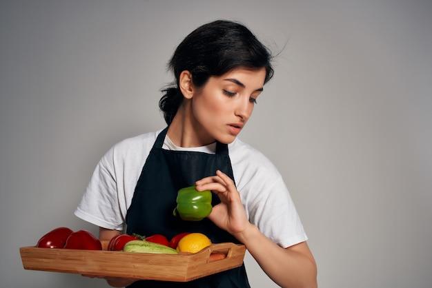 Szef kuchni w czarny fartuch warzywa świeżej żywności na białym tle. zdjęcie wysokiej jakości