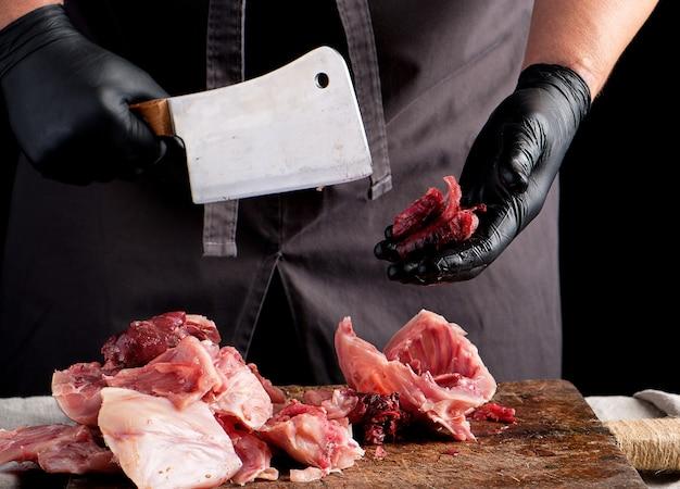 Szef kuchni w czarnych kawałkach lateksu kroi na kawałki surowe mięso królika na brązowej drewnianej desce
