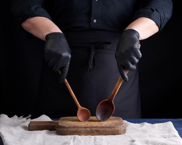 Szef kuchni w czarnych lateksowych rękawiczkach i czarnym mundurze trzyma drewniane zabytkowe łyżki
